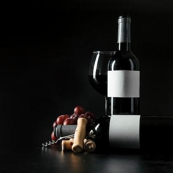 Sacacorchos y uva cerca de botellas y copa de vino