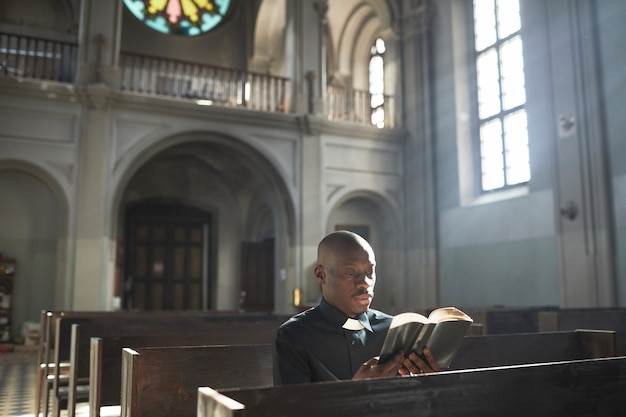 Sacerdote africano en collar sentado en el banco en la iglesia y leyendo la biblia