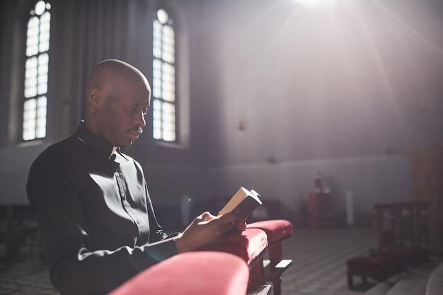 Sacerdote africano sentado frente al altar y leyendo la biblia en la iglesia