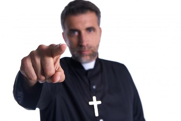 Sacerdote apuntando el dedo al frente como una culpa