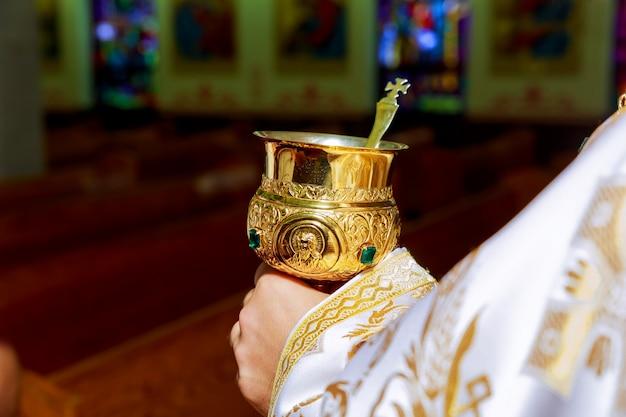 Sacerdote católico con cáliz en la ceremonia de consagración.