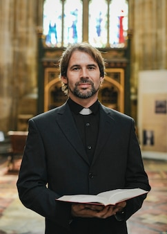 Sacerdote cristiano de pie junto al altar