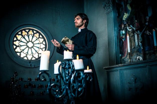 Sacerdote leyendo y orando en la iglesia