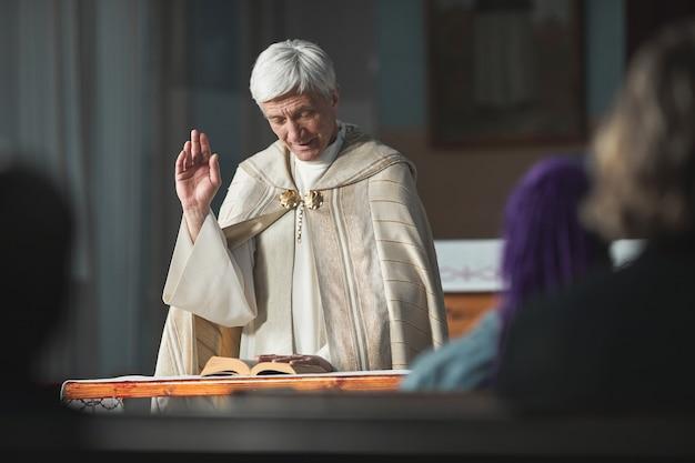 Sacerdote mayor leyendo la biblia para las personas durante la ceremonia en la iglesia
