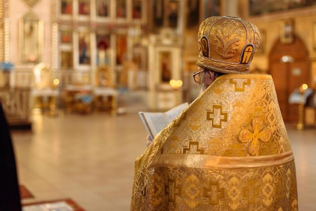 Sacerdote ortodoxo con una túnica dorada en la iglesia cristiana de la resurrección