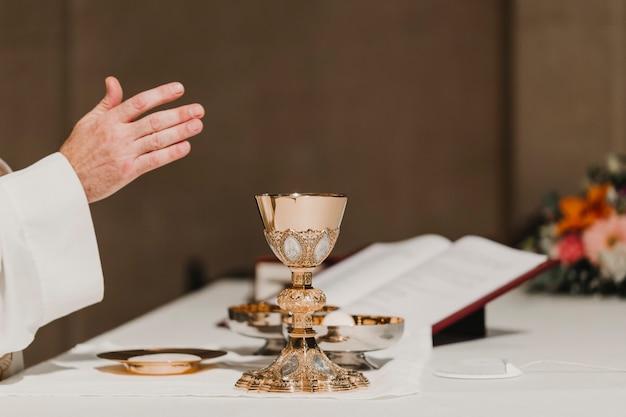 Sacerdote que sostiene la copa durante una ceremonia nupcial de la misa. concepto de religión