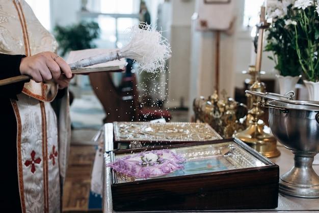 Sacerdote está rociando agua bendita en los anillos de boda en la iglesia