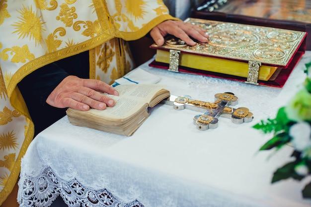 El sacerdote sostiene sus manos sobre los atributos ceremoniales de la boda en el altar en una iglesia