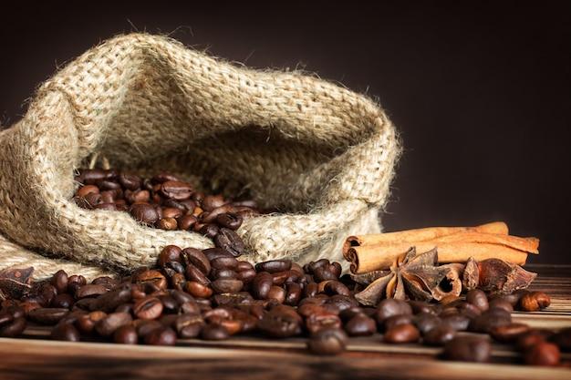 Saco de arpillera gruesa con granos de café espolvoreados sobre una mesa de madera quemada con ramas de canela y estrellas de anís.