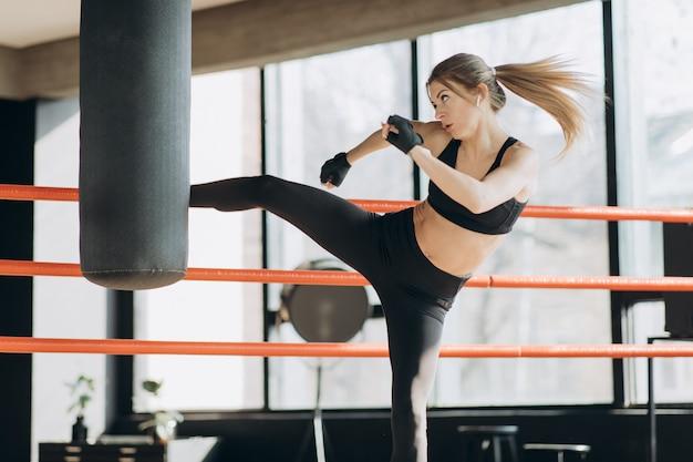 Saco de boxeo de entrenamiento de mujer kickboxing en cuerpo de ajuste de fuerza feroz de fitness