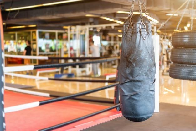 Saco de boxeo negro que cuelga en resumen borroso de gimnasio y boxeo defocused interior y gimnasio h
