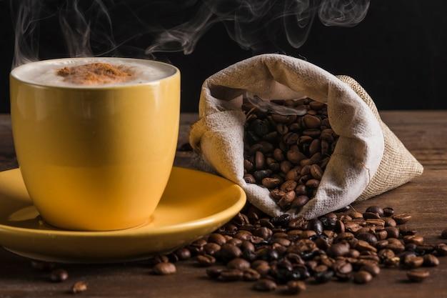 Saco de café y taza amarilla con plato.