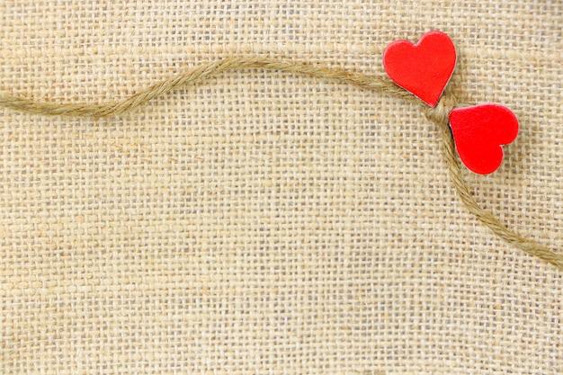 Saco de cuerda pequeña con par de papel rojo corazón sobre fondo de saco marrón