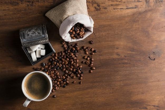 Saco con granos de café cerca de caja para azúcar y taza.