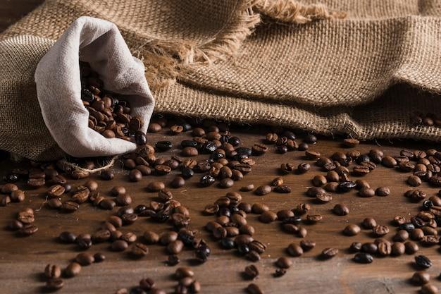 Saco con granos de café en mesa.