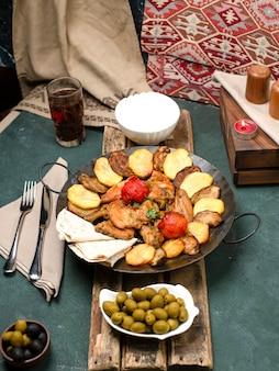 Saco ichi caucásico con carne y papas servidas con yogurt y composto sobre una tabla de madera