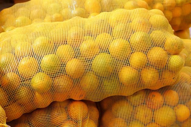 Saco naranja de frutas cítricas apiladas.