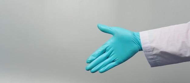 Sacudida de la mano use una bata de médico y un guante médico azul sobre fondo gris. estudio de rodaje.