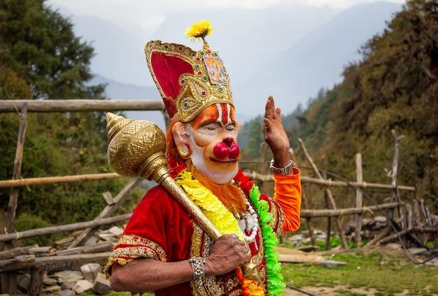 Sadhu con una cara pintada tradicional con máscara y un atributo religioso especial en katmandú en nepal, foto editorial