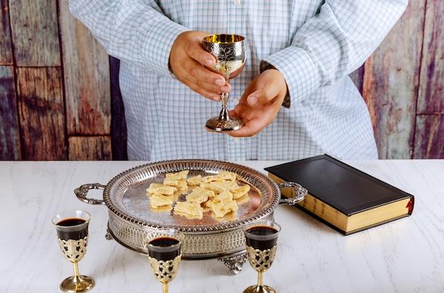 Sagrada comunión copa de vino tinto, pan, oración bíblica por vino y santa biblia.