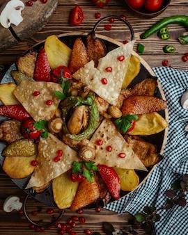 Saj de pollo con patata, berenjena, pimiento rojo, trozos de pan plano