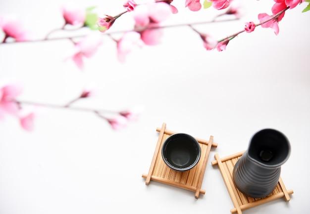 Sake japonés y flor sakura sobre fondo blanco estilo de bebida oriental