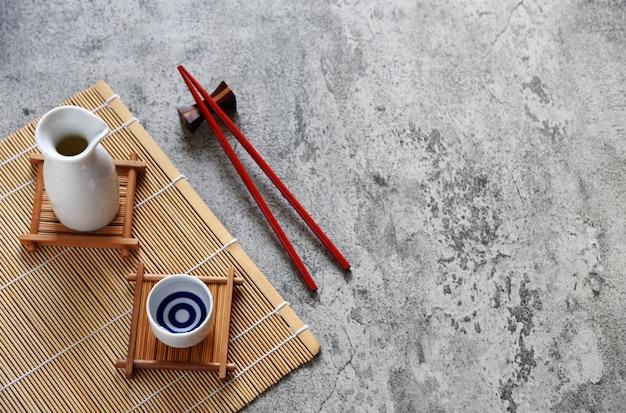 Sake japonés puesto estilo bebida oriental y palillos sobre la mesa