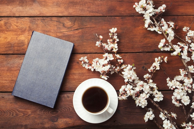 Sakura ramas con flores, taza blanca con café negro y libro sobre una superficie de madera oscura. vista plana, vista superior