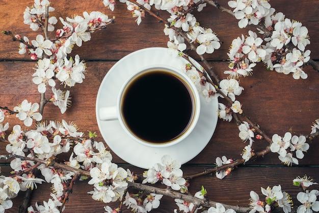Sakura ramas con flores, taza blanca con café negro sobre una superficie de madera oscura. vista plana, vista superior
