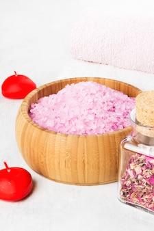 Sal de baño con aroma a rosa en un tazón de madera, pétalos y una rosa rosa fresca, toallas y velas sobre un fondo blanco.