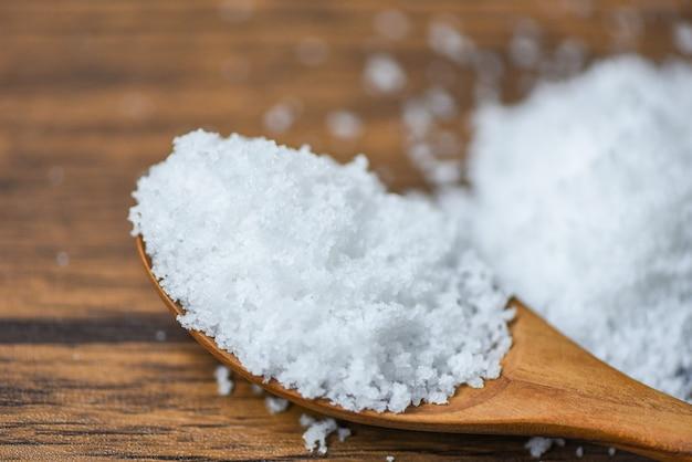 Sal en cuchara de madera y montón de sal blanca de fondo