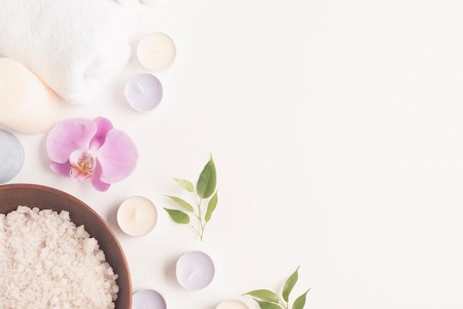 Sal de baño con flor de orquídea y velas sobre fondo blanco