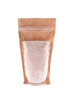 Sal del himalaya, molida en una bolsa de papel marrón. doy-pack con ventana de plástico para productos a granel. de cerca. fondo blanco. aislado.