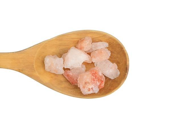 Sal del himalaya rosa en una cuchara de madera aislado sobre fondo blanco.