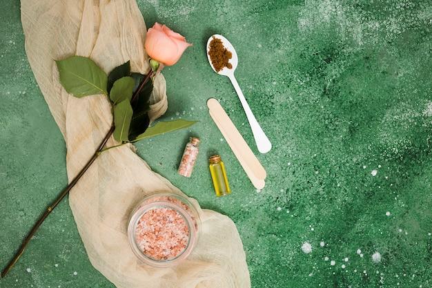 Sal de himalaya rosa en tarro; rosa; aceite esencial y café molido en una cuchara contra el fondo de textura verde.