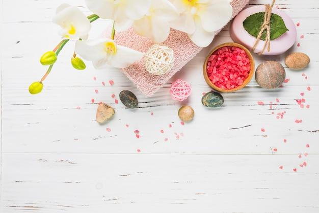 Sal; jabón; piedras de spa; toalla y flores en superficie de madera.