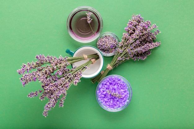 Sal de mar violeta lavanda con flores de lavanda frescas y secas, aceite esencial líquido sobre fondo de color verde. tratamiento de aromaterapia. cosméticos de spa de baño para el cuidado de la piel, boticario de lavanda.