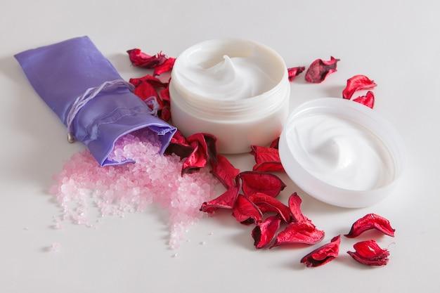 Sal marina rosa y crema facial hidratante sobre una mesa