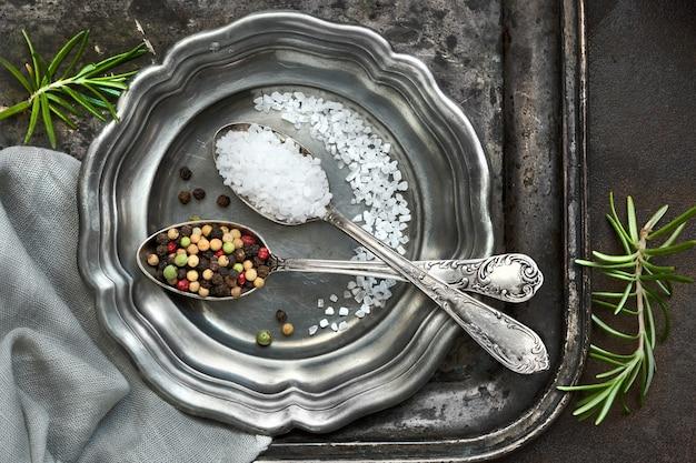 Sal en pimienta mezclada en cucharas vintage en una placa de metal vieja con servilleta de lino en gris oscuro