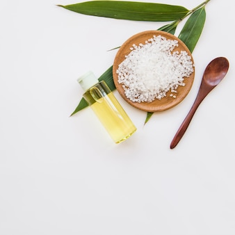 Sal de roca; hojas; cuchara y botella de spray de aceite esencial sobre fondo blanco