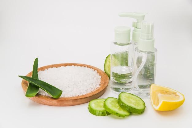 Sal de roca en placa de madera; rebanadas de pepino; botella de limón y spray sobre fondo blanco