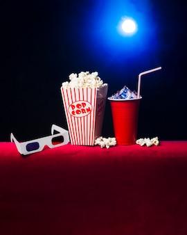 Sala de cine con paquete de palomitas y gafas 3d