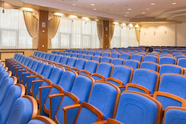 Sala de conferencias con asientos azules.