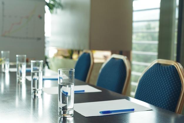 Sala de conferencias interior con sillas vacías.