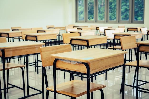 Sala de conferencias o aula vacía de la escuela con escritorios silla de madera de hierro para estudiar lecciones en la escuela secundaria