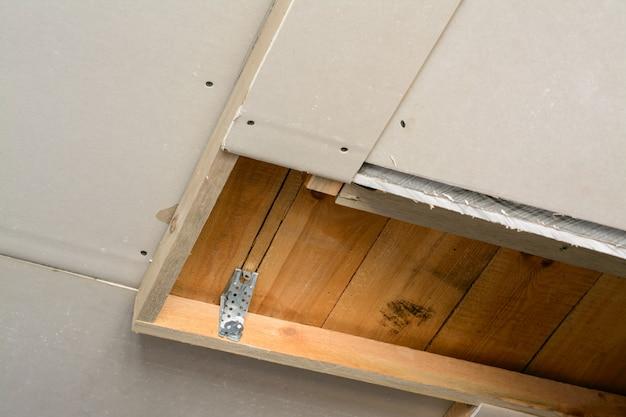 Sala de construcción con paneles de yeso. hacer techo suspendido con marco de madera y paneles de yeso en una casa privada