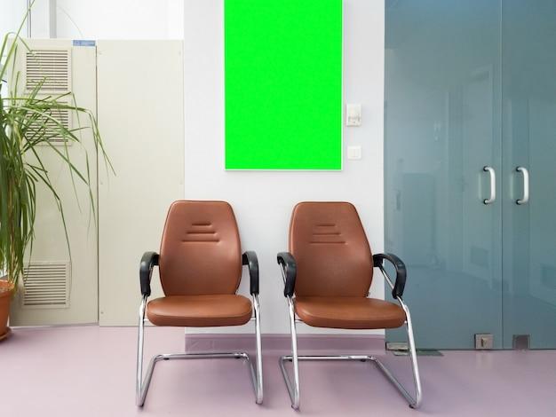 Sala de espera en el hall del hospital con un tablero de pantalla verde. maqueta lista