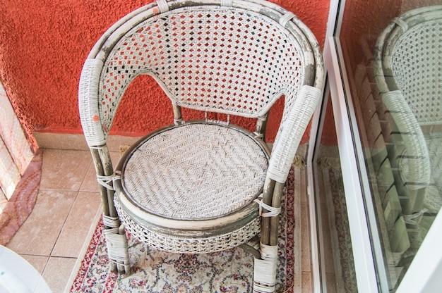 Una sala de estar en el balcón con una silla de mimbre de ratán, una alfombra. vista superior