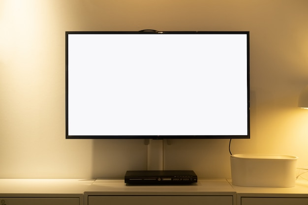 La sala de estar llevó una pantalla de tv en blanco en un muro de concreto con una mesa de madera y un reproductor multimedia