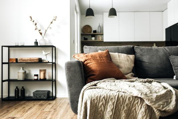 Sala de estar luminosa de espacio abierto con cómodo sofá, tela escocesa de punto, almohada de jengibre, cocina, piso de madera.